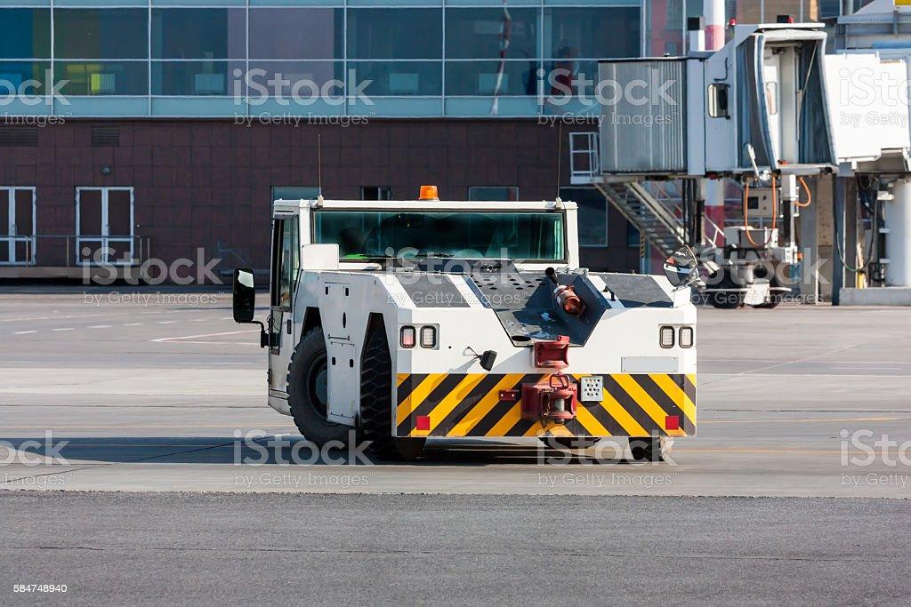 Airplane tow tractor near passenger boarding bridge royalty-free stock photo