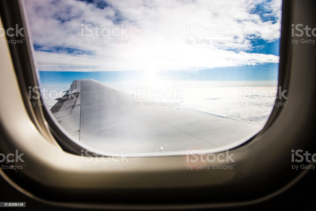 Airplane window during an international travel flight stock photo