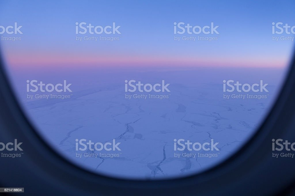 Airplane Window View of the Arctic Landscape at Dusk stock photo