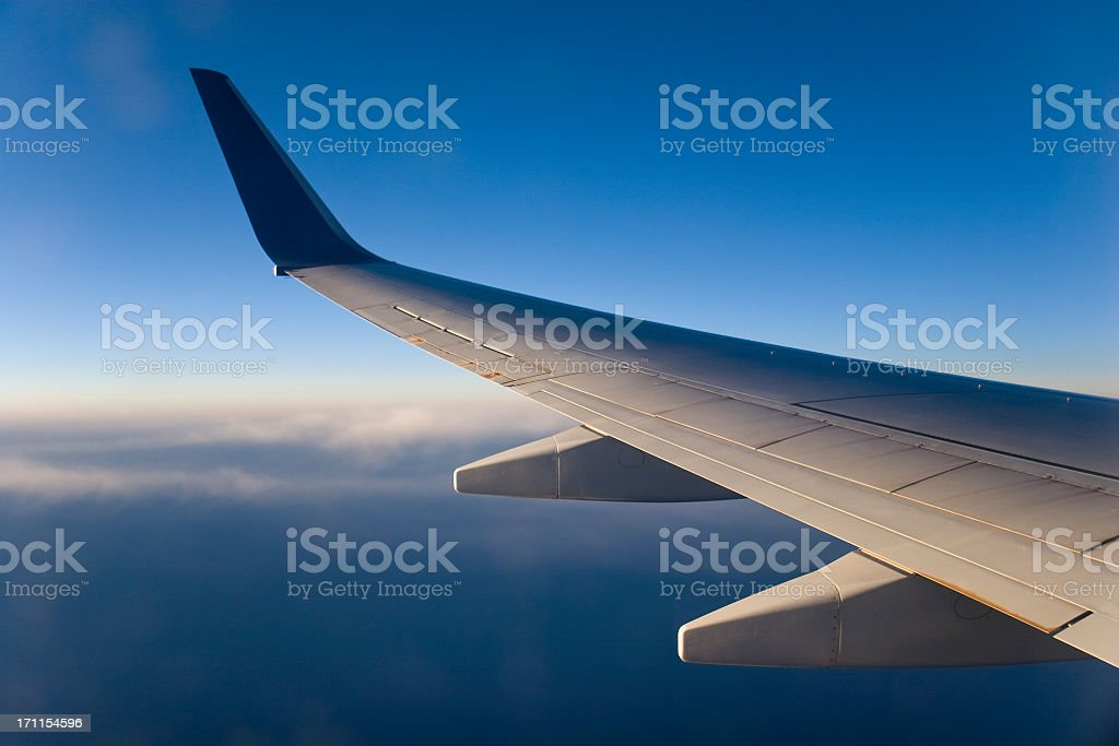 Airplane wing above the clouds during flight royalty-free stock photo