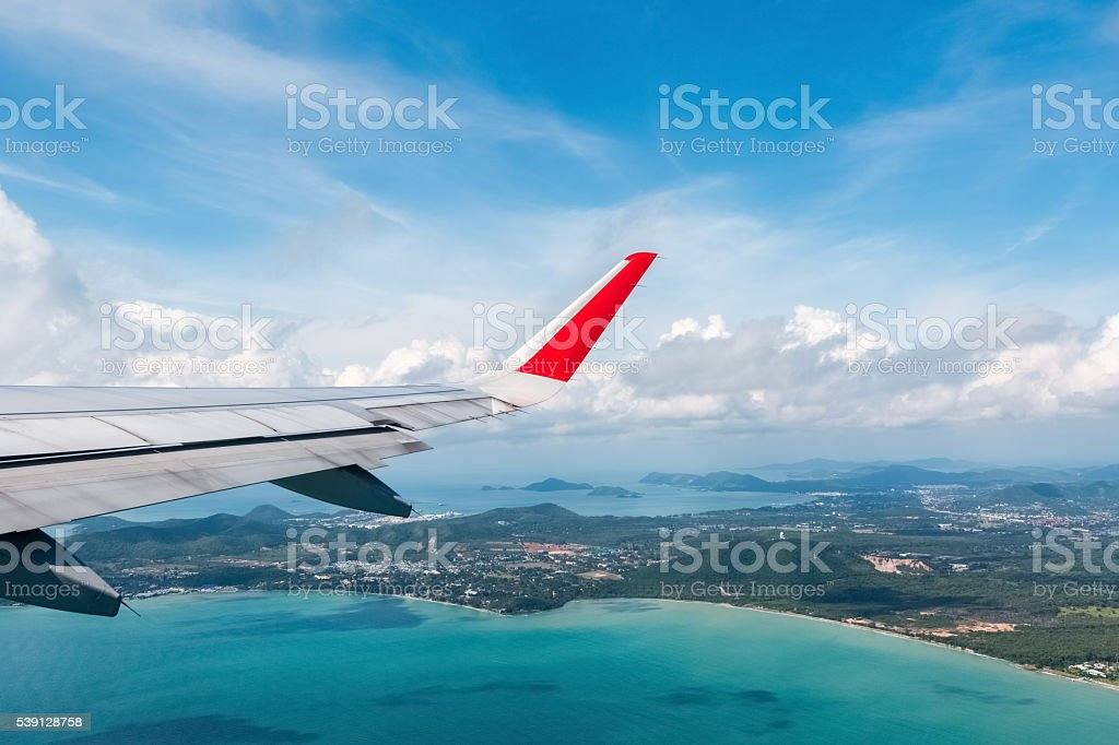 airplane wing above the seashore stock photo