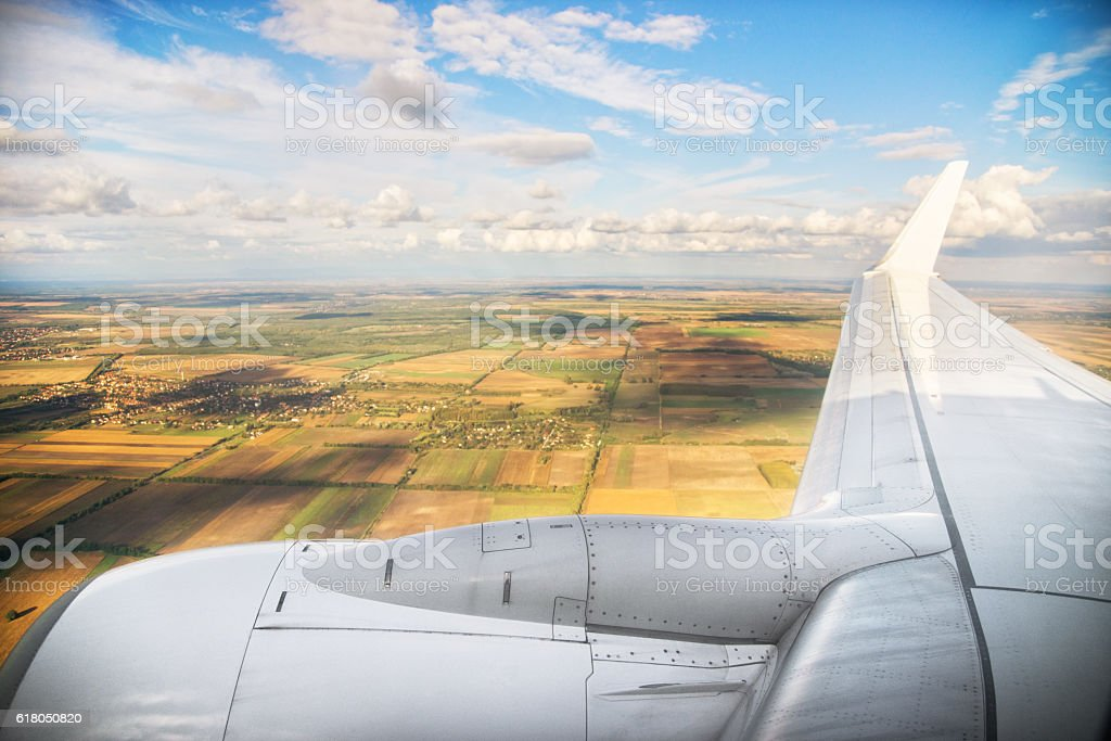 Airplane wing flying above the fields in Hungary stock photo