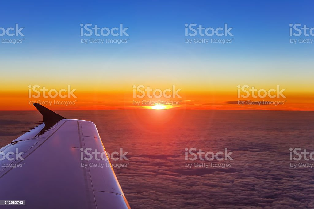 Airplane wing in flight above the clouds at the sunset background stock photo