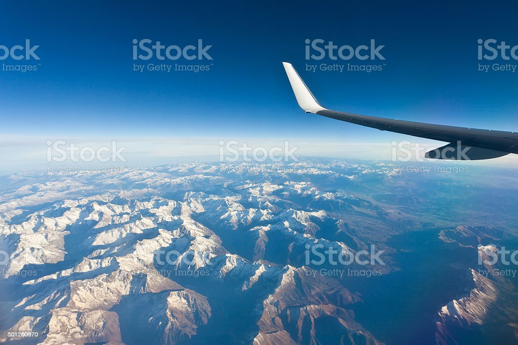 Airplane Wing in Flight above the mountain stock photo