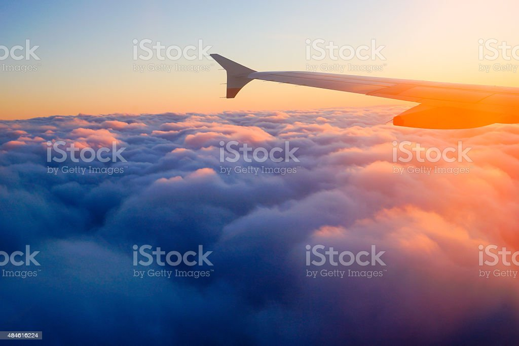 Airplane Wing in Flight from window, sunset sky stock photo