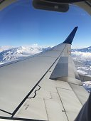 airplane wing in flight over mountains