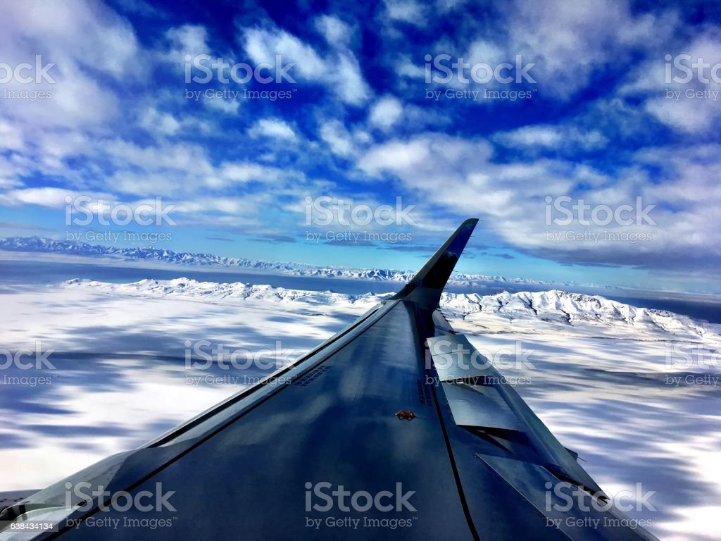 airplane wing over mountains stock photo