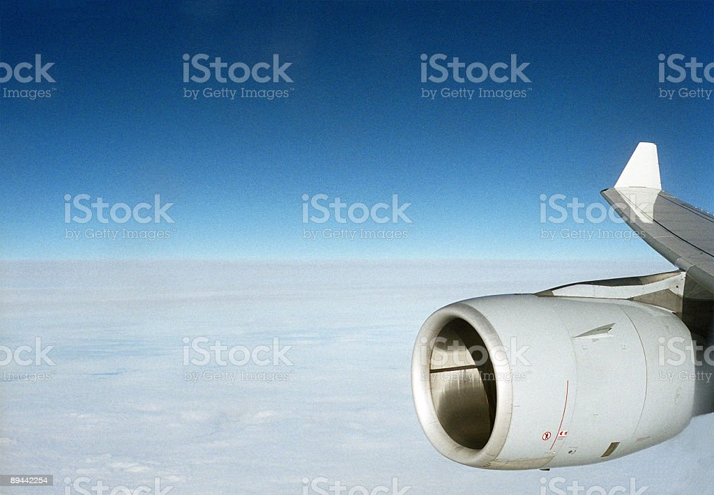 Airplane wing with engine before blue sky. royalty-free stock photo