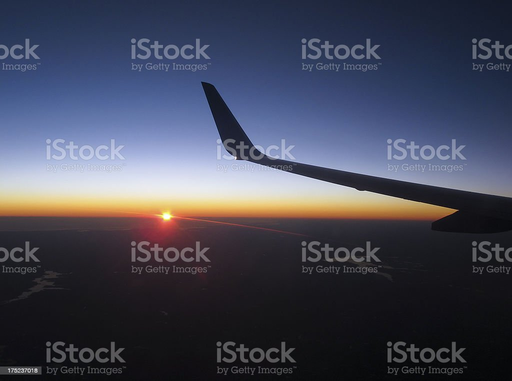 Airplane wing with sunset in the background royalty-free stock photo
