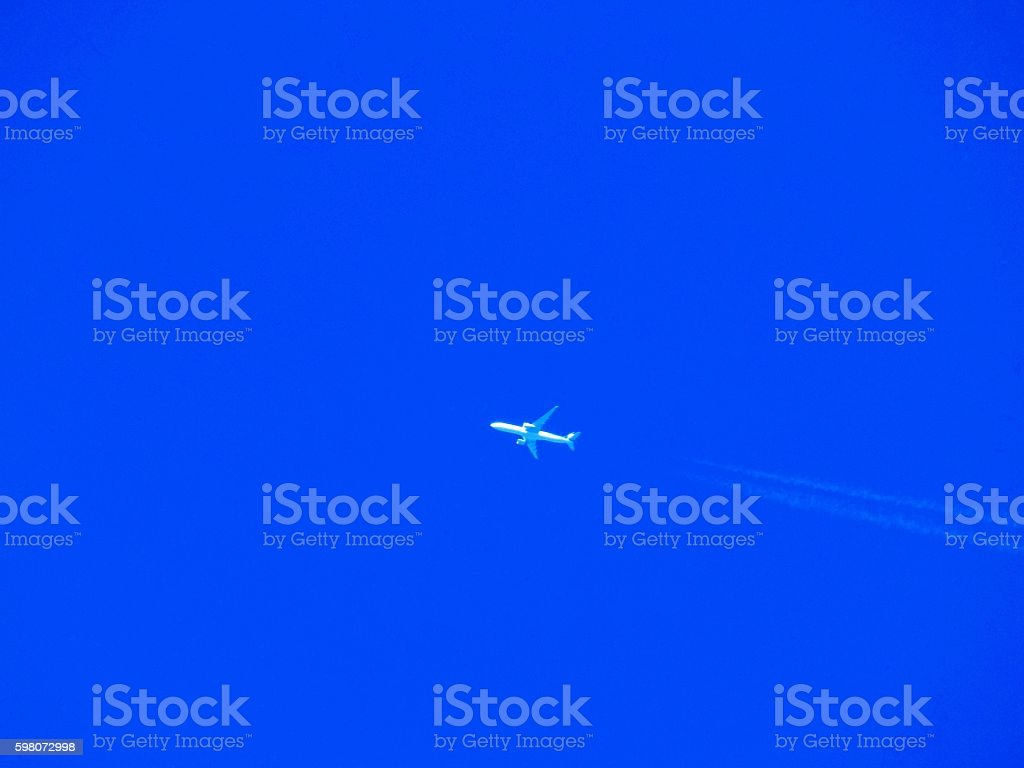Airplane with chemtrails on blue sky stock photo