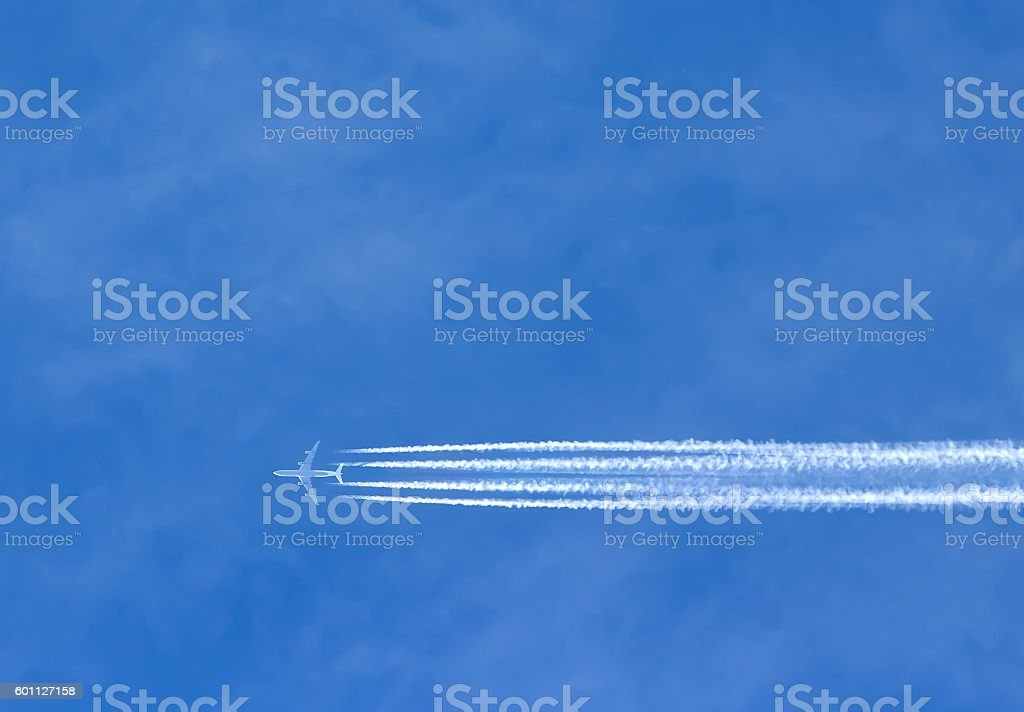 Airplane with contrails in clear blue sky, Cruising altitude stock photo