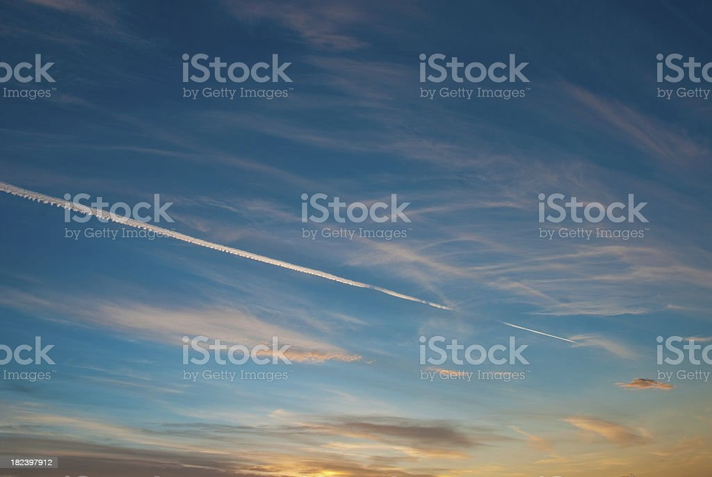 Airplane with vapor stripes flying into beautiful sunset royalty-free stock photo