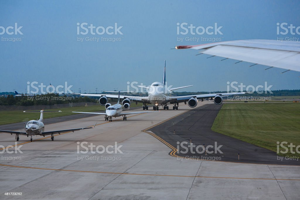 Airplanes big and small lining up on runway for take-off stock photo