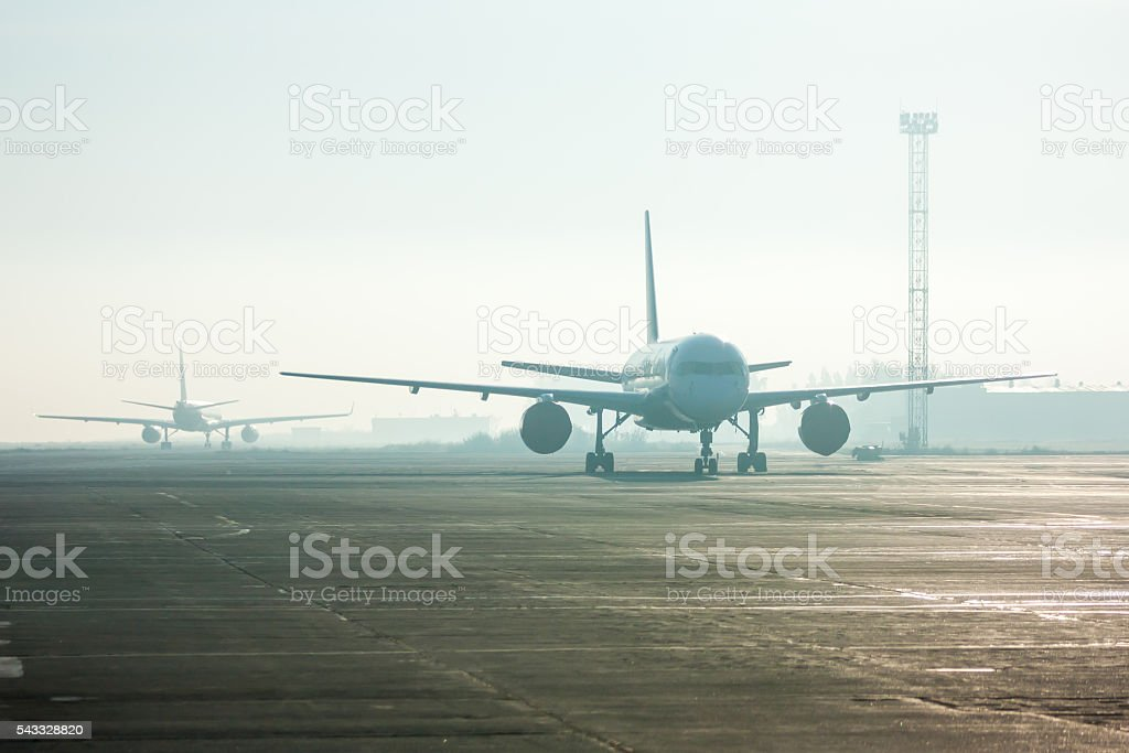 Airplanes in the fog on the airport apron royalty-free stock photo