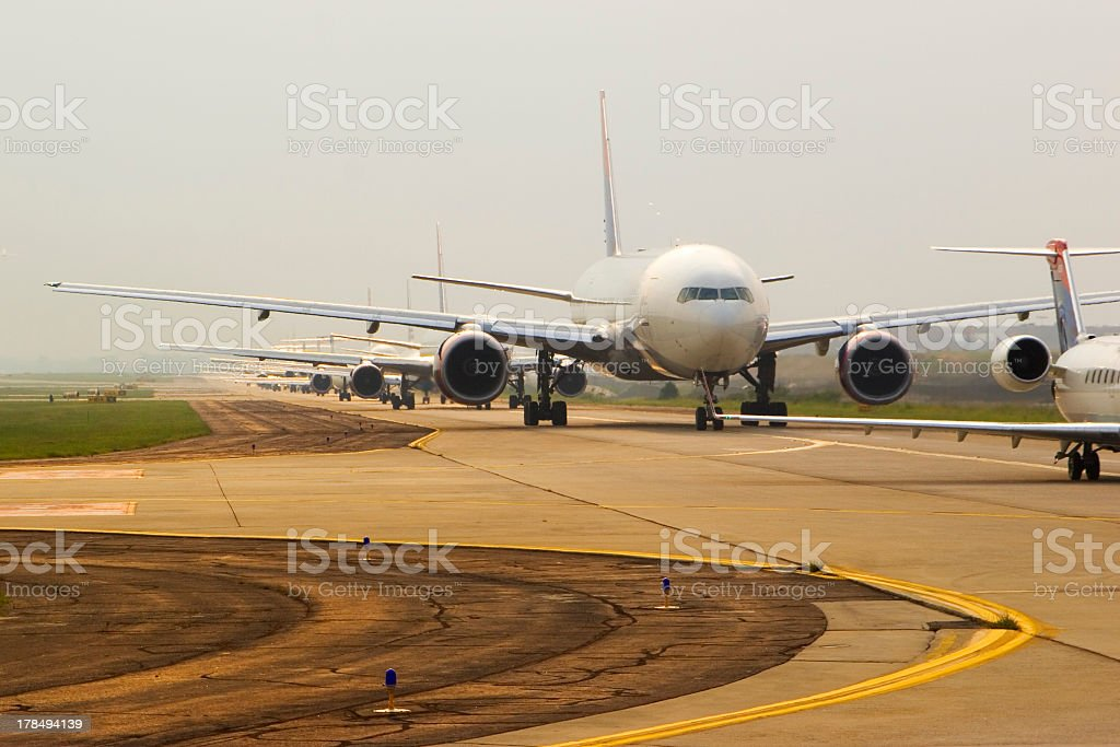 Airplanes taxiing down the runway stock photo