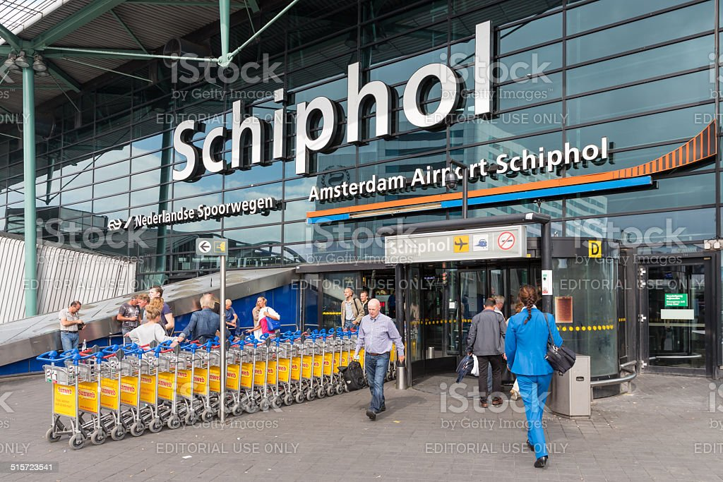 Airport entrance with passing travellers at the airport of Amsterdam stock photo