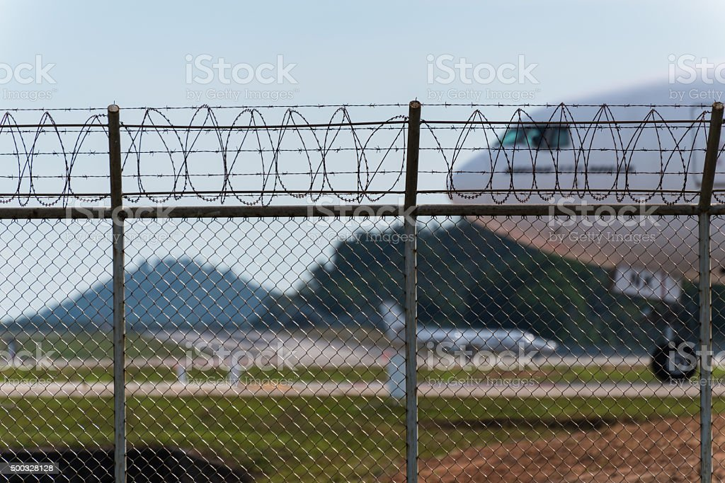 Airport fence and air plane behind stock photo