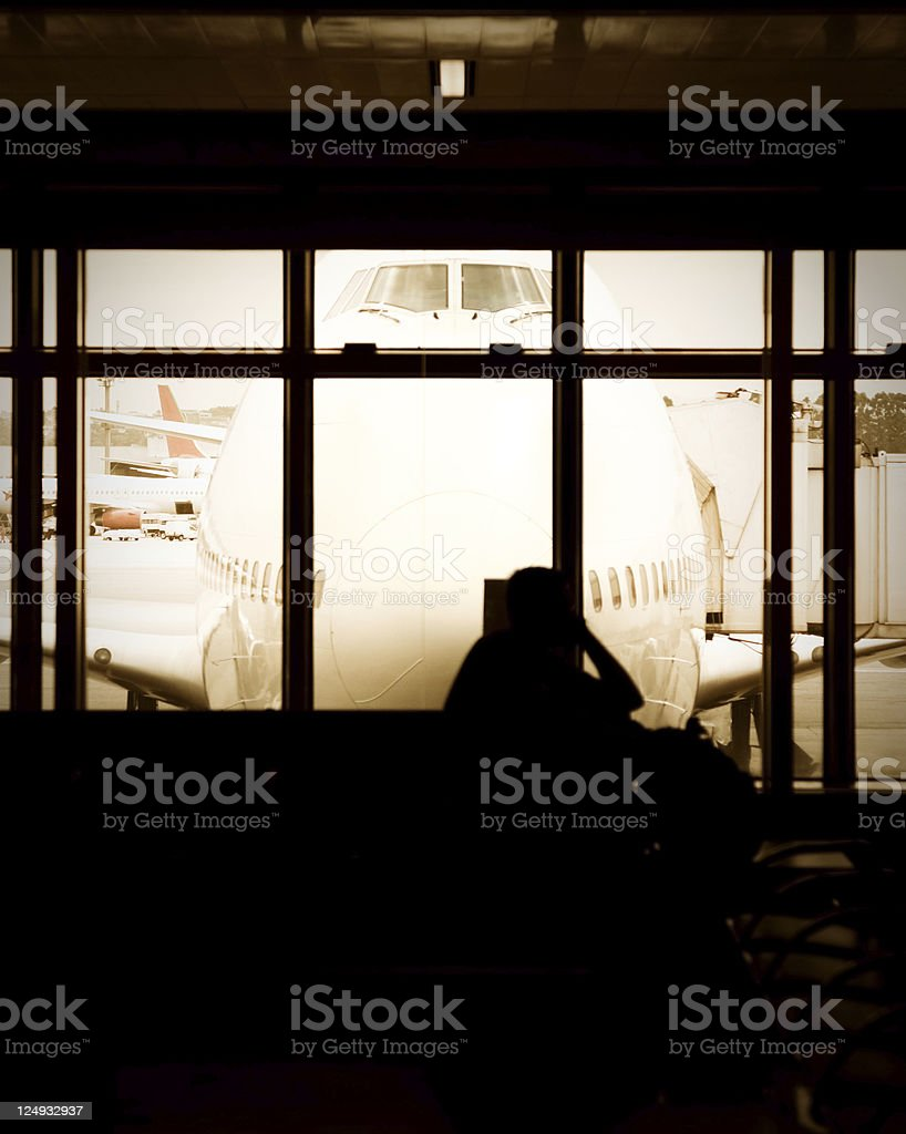 Airport gate, waiting hall, unrecognisable person, airplane outside - sunset royalty-free stock photo