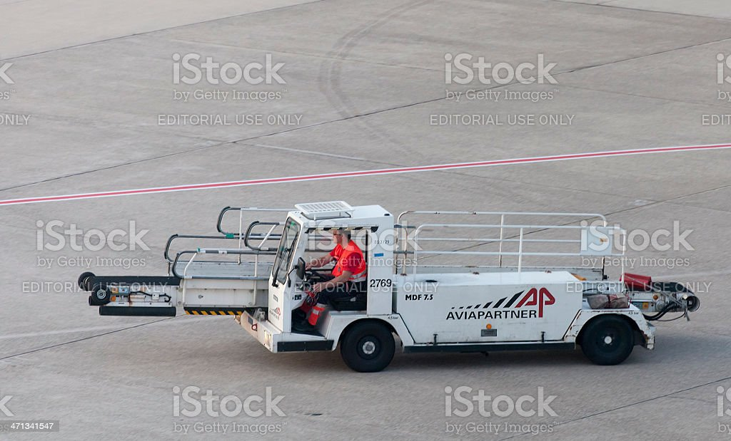 Airport ground technician driving vehicle for loading luggage royalty-free stock photo