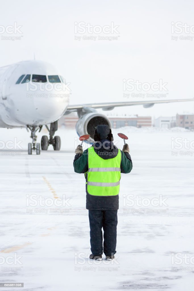 Airport marshaller meets the aircraft that parking in a cold winter weather stock photo