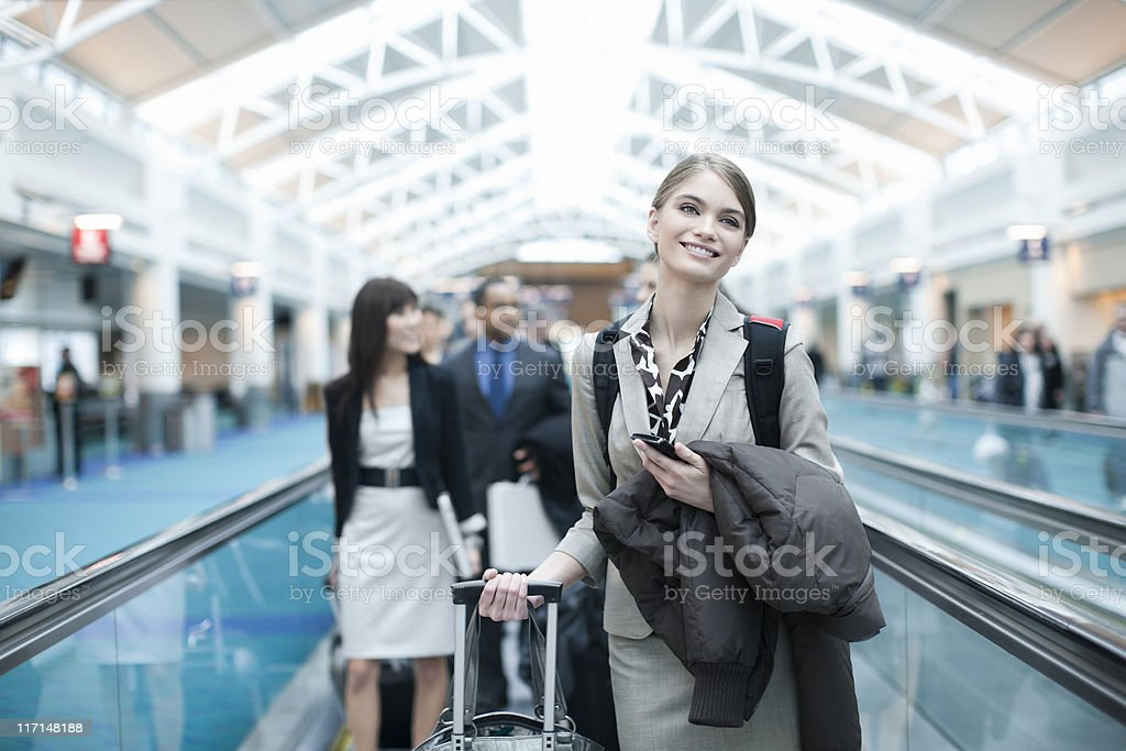 Airport Moving Walkway with Smiling Businesswoman Holding Cell, Copy Space stock photo