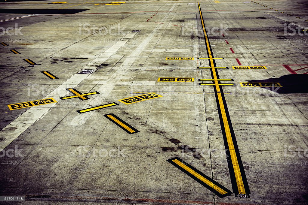 Airport runway with yellow marking lines and lane numbers stock photo