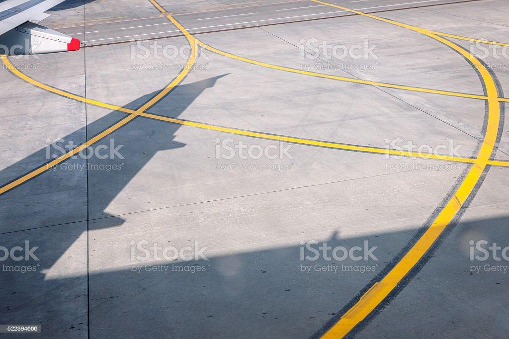 Airport Runway,shadow, red, gray, airplane wing, yellow stock photo