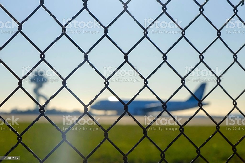 airport security mesh fence with control tower stock photo
