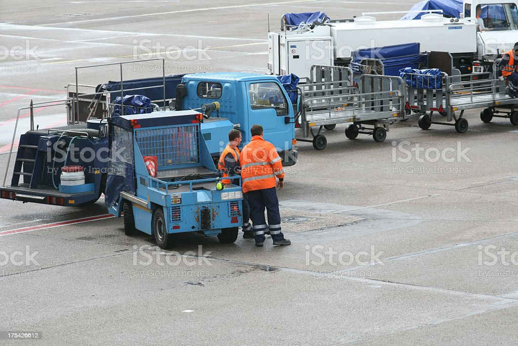Airport service in orange shirts standing by blue vehicles stock photo