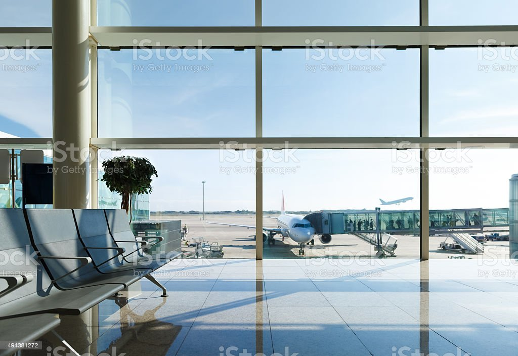 Airport terminal, people going to airplane in background stock photo