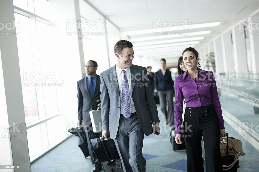 Airport with Business Team Walking, Pulling Luggage and Smiling royalty-free stock photo