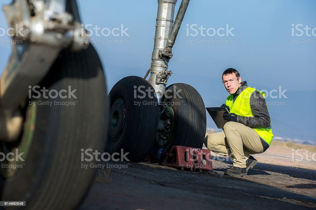 Airport worker checking chassis stock photo