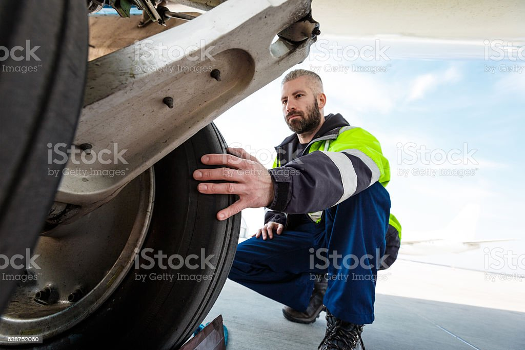 Airport worker checking tires stock photo