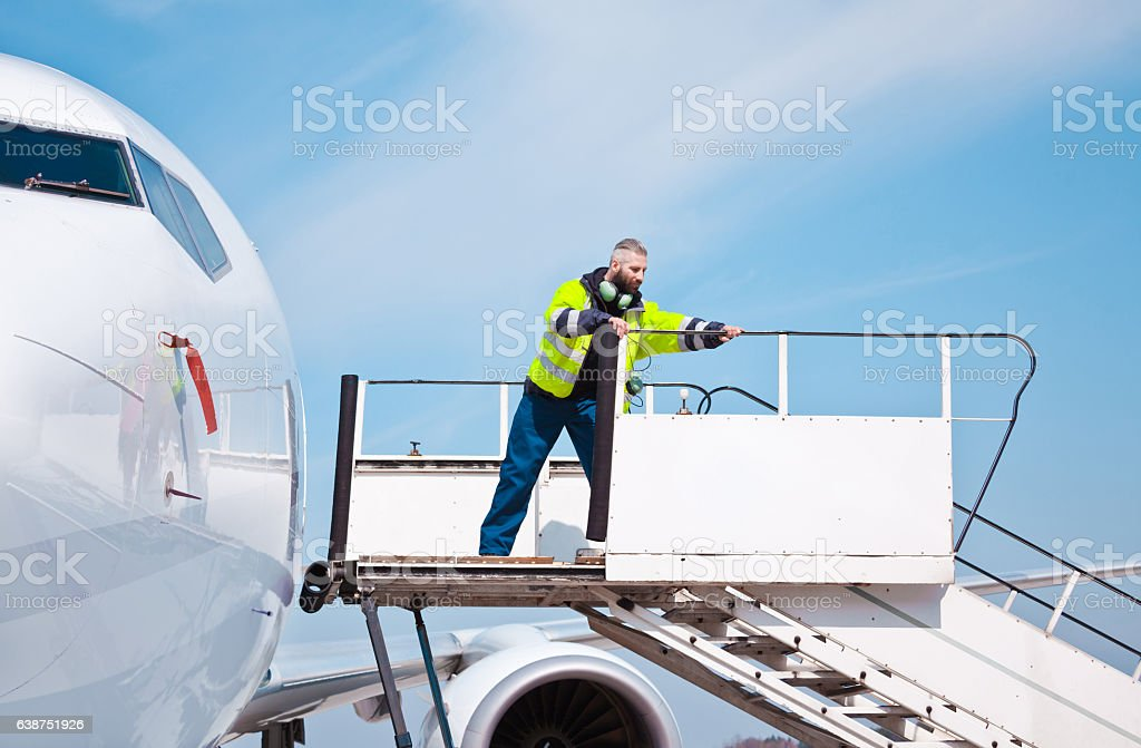 Airport worker on the aircraft stairs stock photo