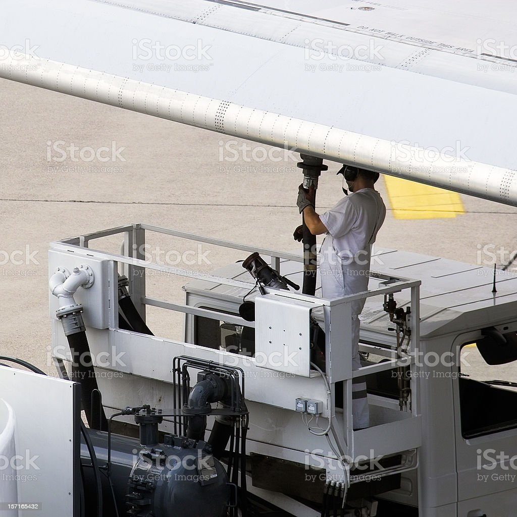 Airport worker refuelling an aeroplane before take off stock photo