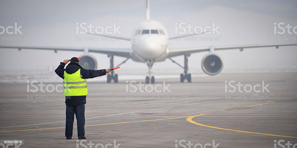 airport worker signaling stock photo