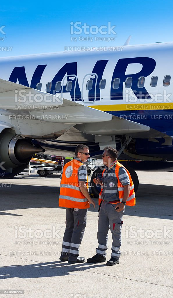 Airport Workers Chat on Tarmac at Rome's Fiumicino Airport stock photo