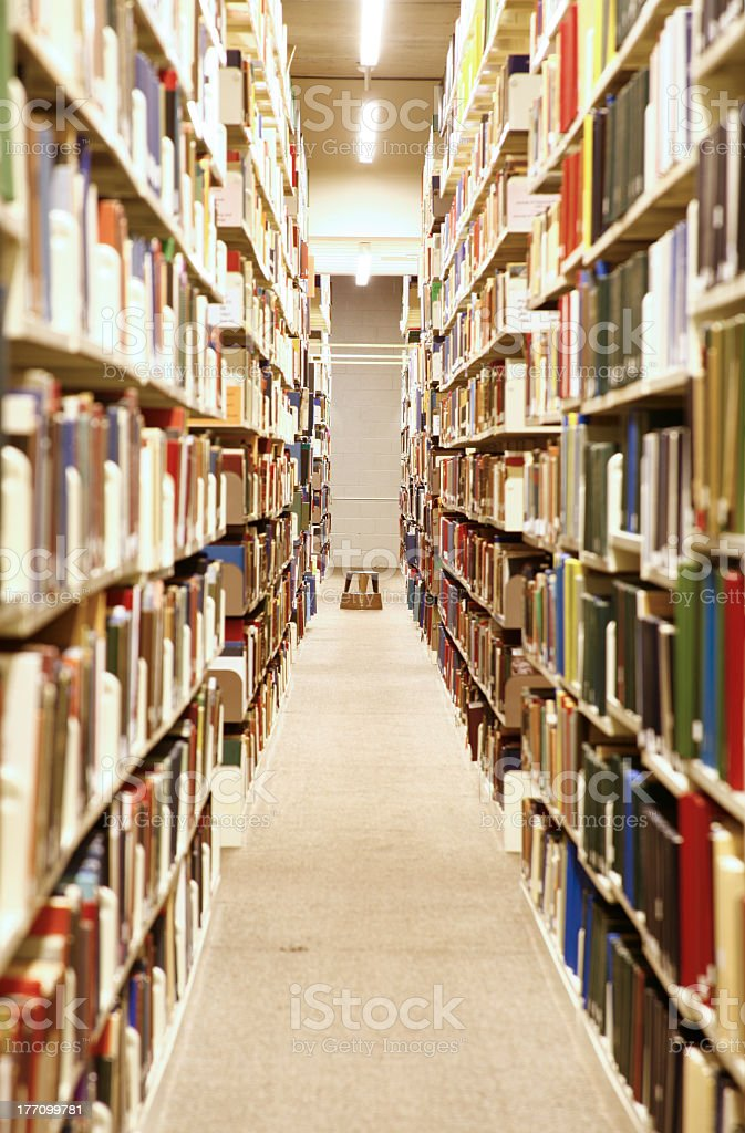 Aisle between tall bookshelves in a library royalty-free stock photo