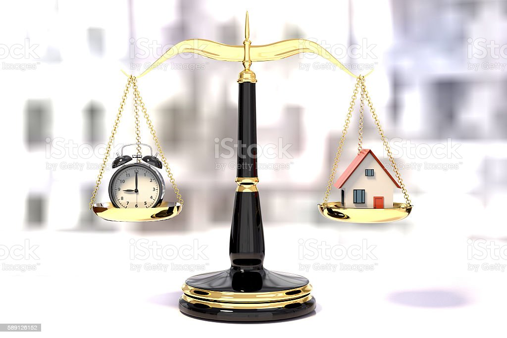 alarm clock and house on a golden law scale stock photo