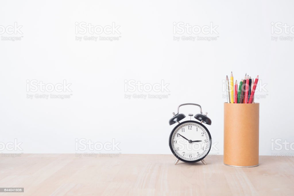 alarm clock and pencil on wood table with copy space stock photo