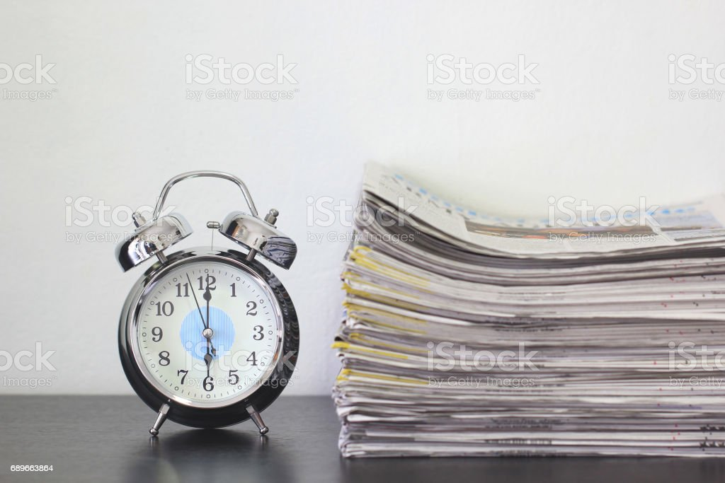 Alarm clock and stacking of Newspaper on wooden table, time and global communications concept stock photo