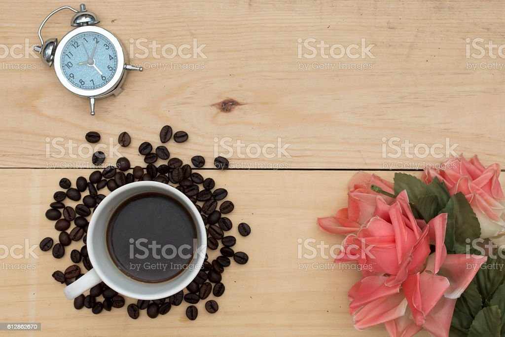 alarm clock, coffee and flowers on wood table. stock photo