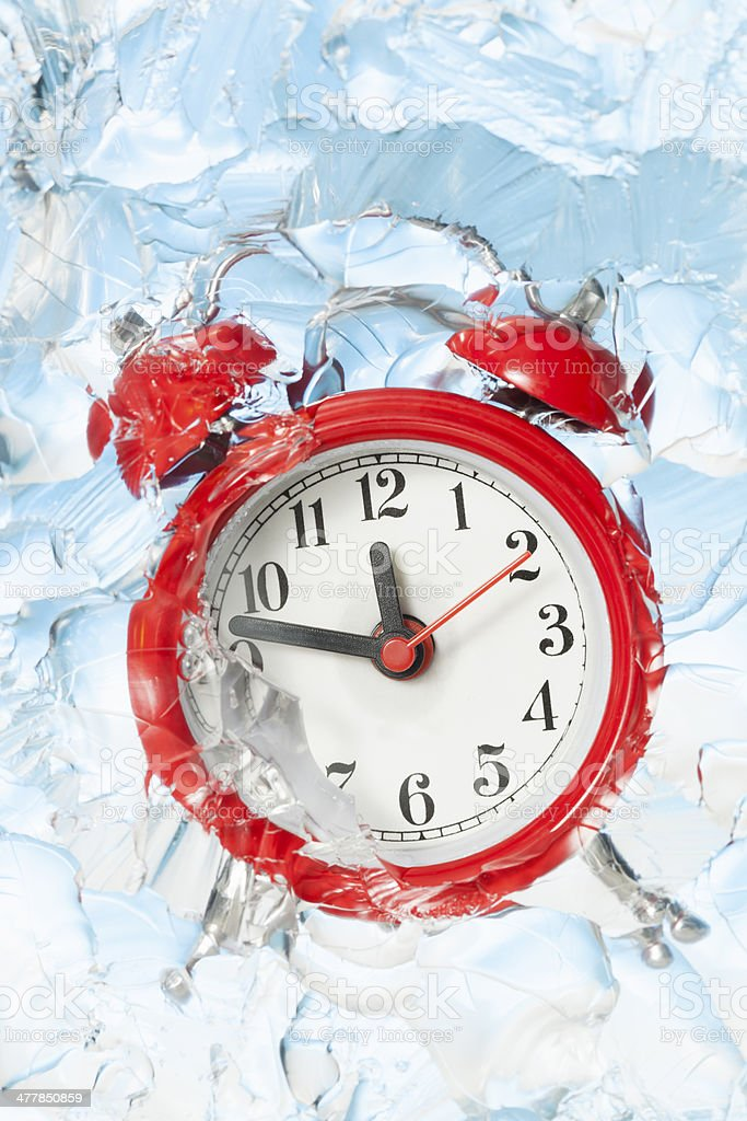 Alarm clock frozen in a block of ice stock photo