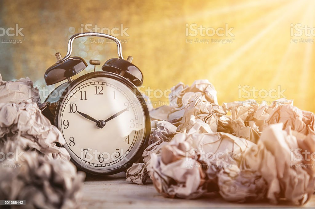 Alarm clock in a wastepaper concept stock photo