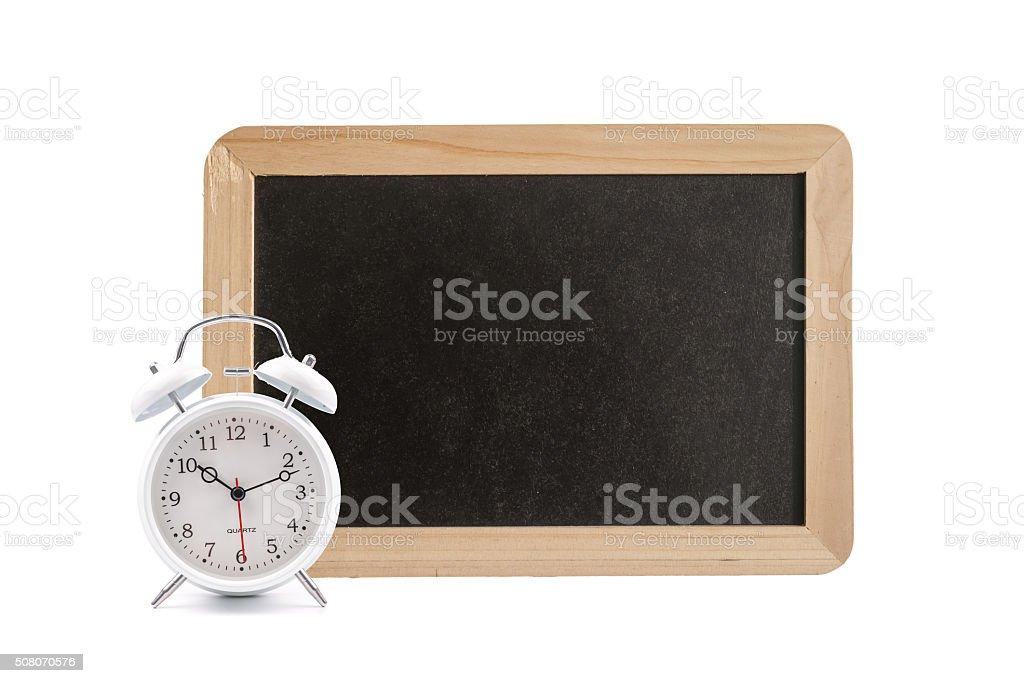 alarm clock in front of blackboard stock photo