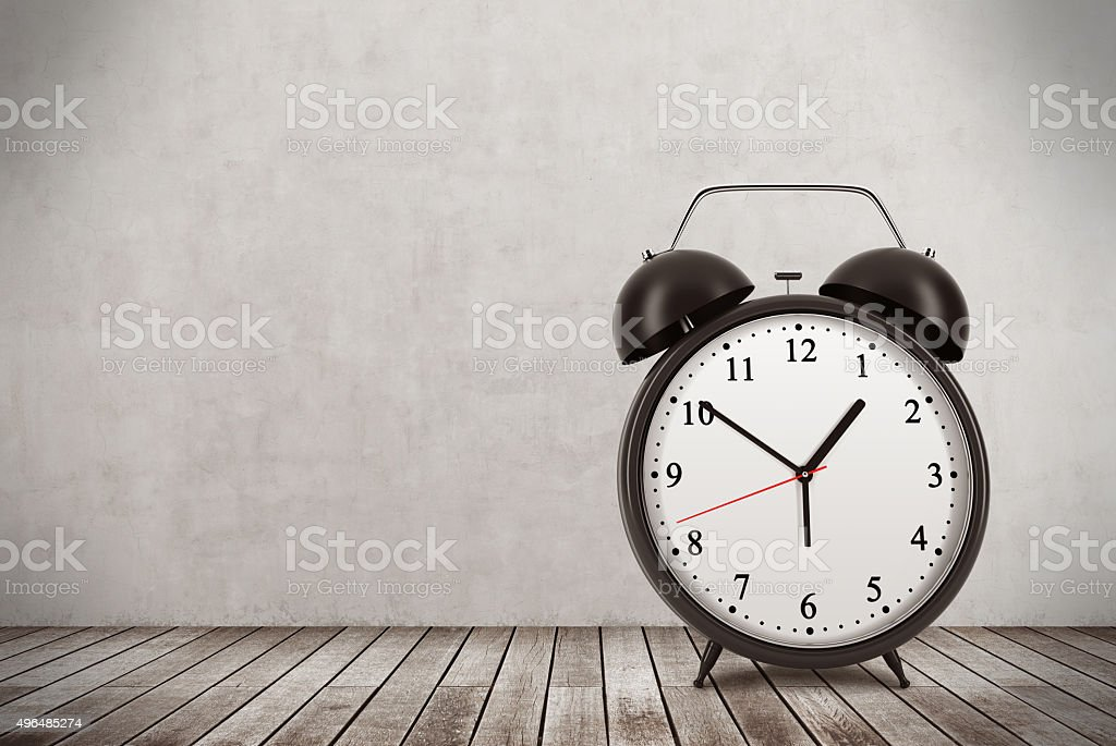 alarm clock is on the wooden floor. Concrete wall. stock photo