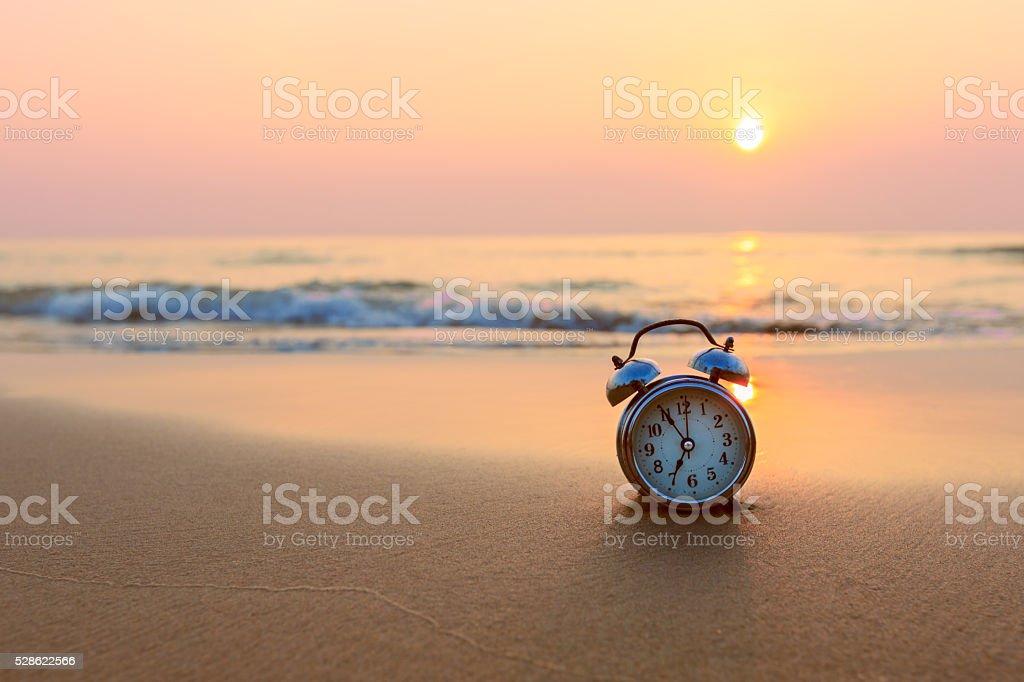 Alarm clock on beach stock photo