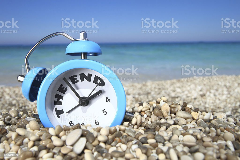 Alarm clock on beach signaling end of summer royalty-free stock photo