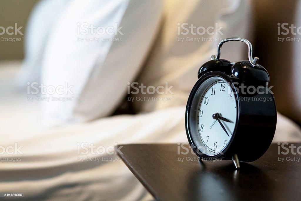 alarm clock on bedside stock photo