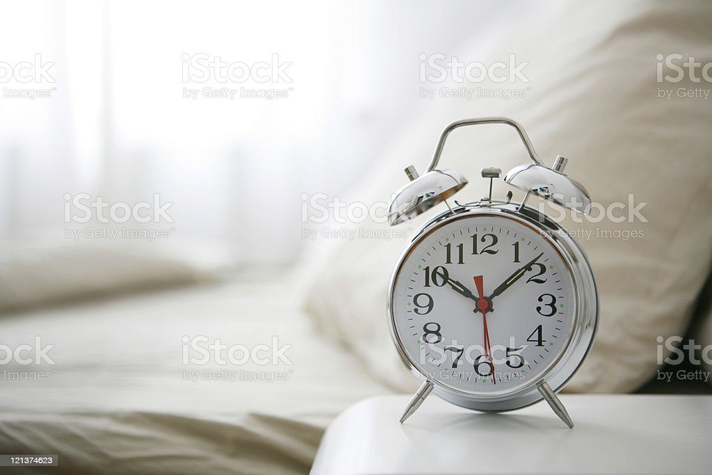 Alarm Clock on bedside table stock photo